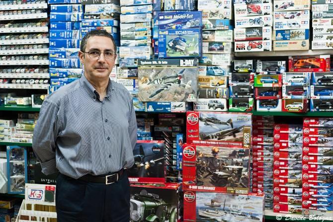 Carmelo Filippone del negozio Effemodel posa davanti ad una parete colma di kit di modellismo