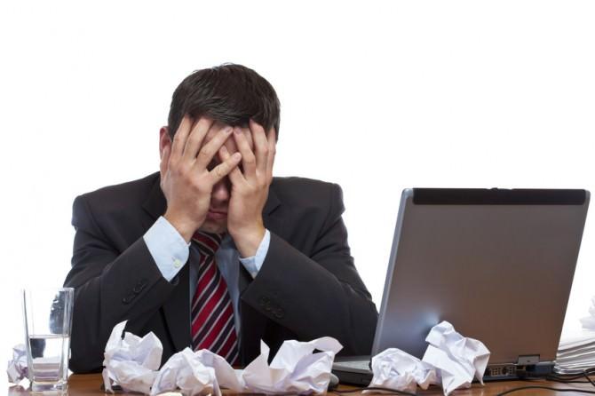 Mann sitzt verzweifelt über Papierflut am Arbeitsplatz