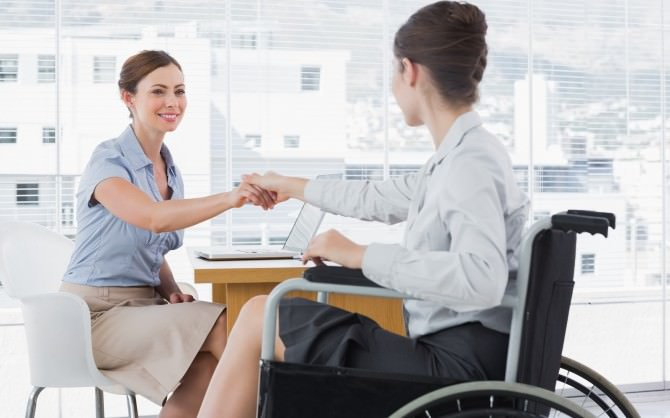 Businesswoman shaking hands with disabled colleague at desk in o